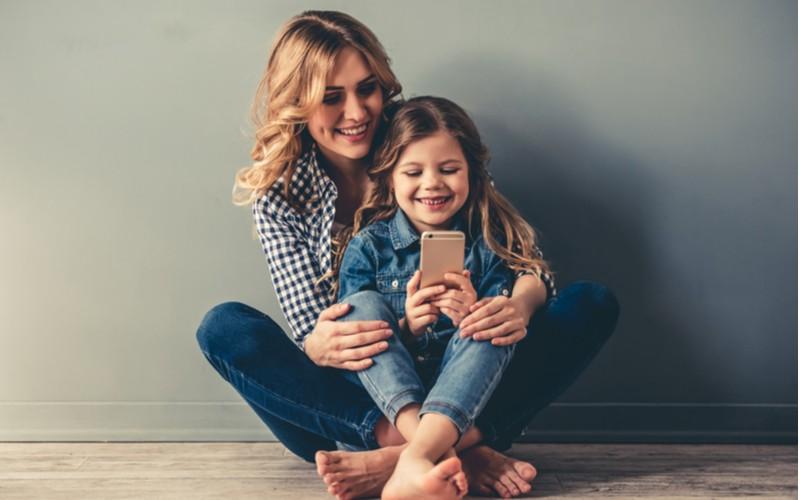 Dítě a máma v riflích sedící na podlaze