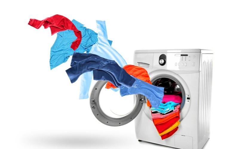 Nejlepší pračky (pračka a létající oblečení na modrém pozadí)