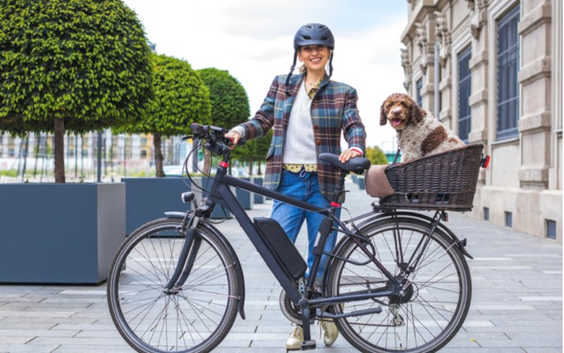 Městský elektrokolo, žena a pes v košíku