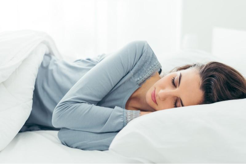 Žena spí na posteli s matrací a polštářem