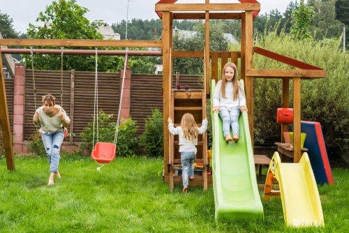 Máma se dvěma dcerami na dětském hřišti na zahradě