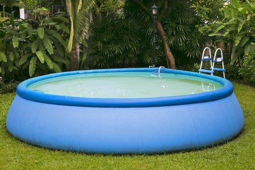 Modrý kruhový bazén se schůdky na zahradě