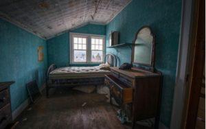 Starý, špinavý matraci na posteli v pokoji za přirozeného světla