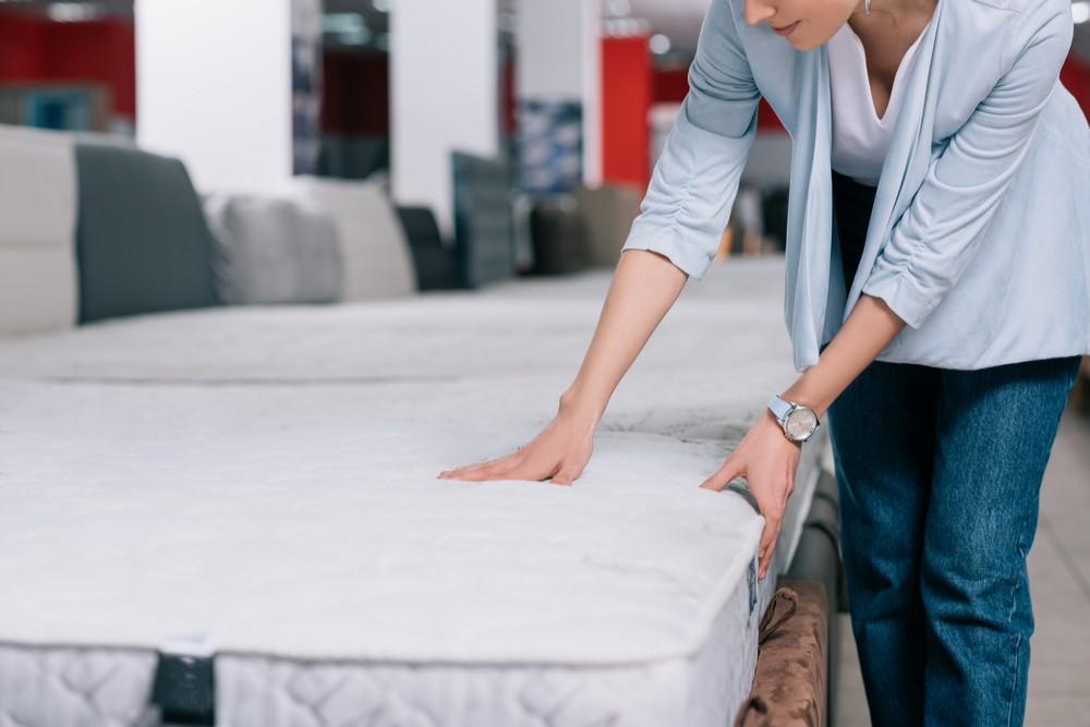 Žena vybírá matraci v prodejně