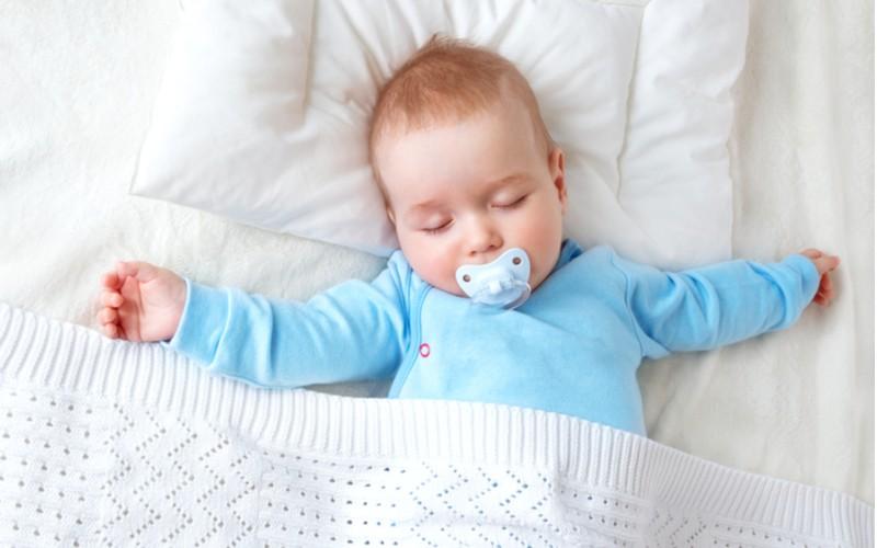 Miminko spící v postýlce na bílém polštáři