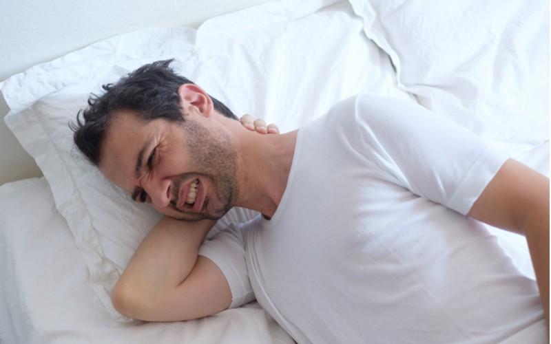 muž s bolestí v krku v posteli na polštáři