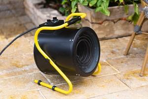 černý ohřívač do dílny se žlutým podstavcem