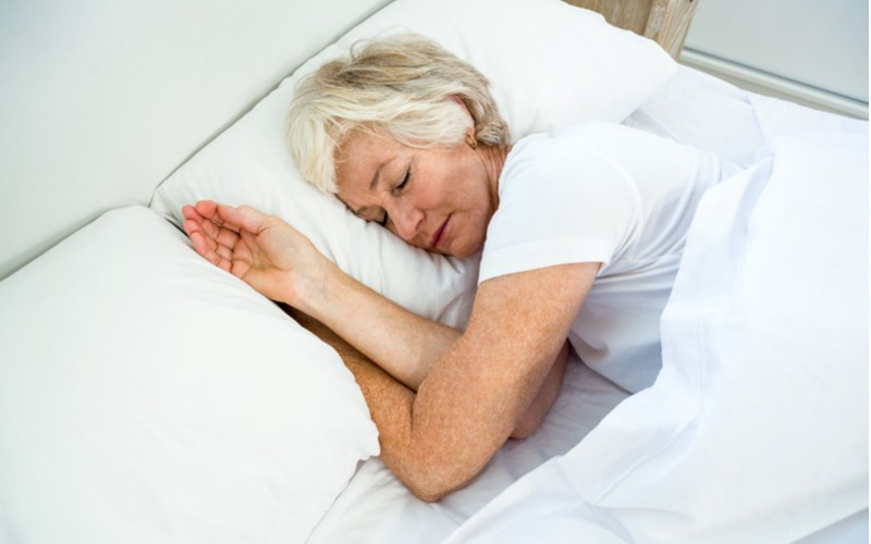Starší žena klidně spí na posteli
