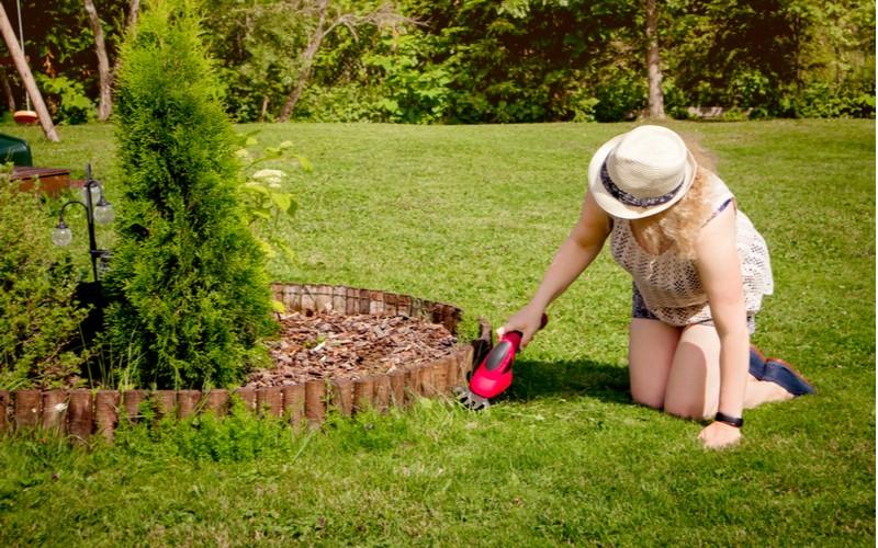 žena používá elektrické nůžky na trávu v zahradě