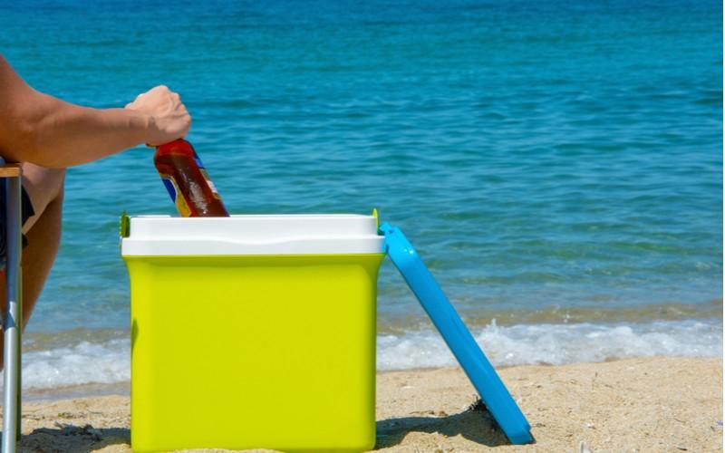 Chlap vytahuje pivo z barevné přenosné ledničky u moře