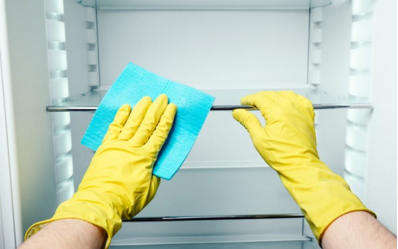 Čištění lednice v rukavicích hadříkem