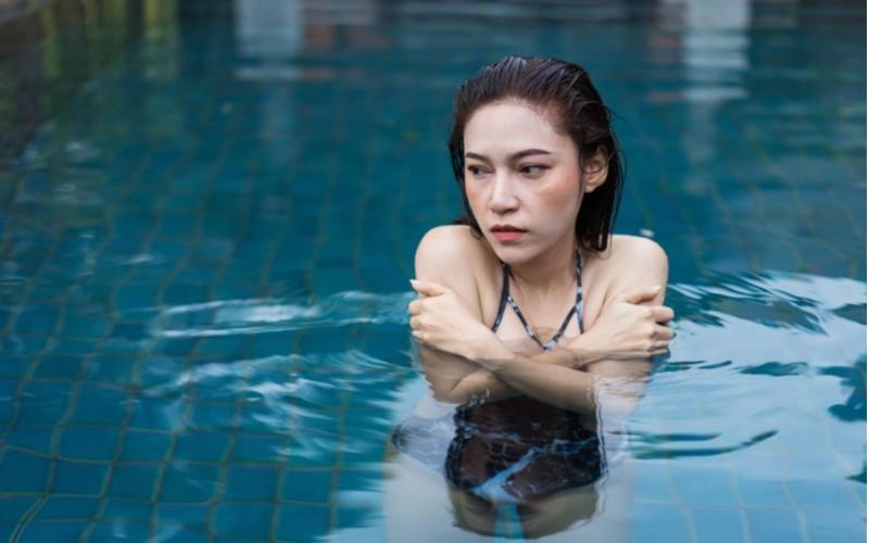 žena mrznoucí ve studené vodě bazénu