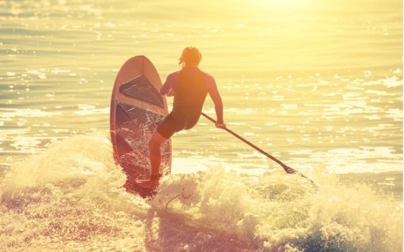 muž surfující na paddleboard