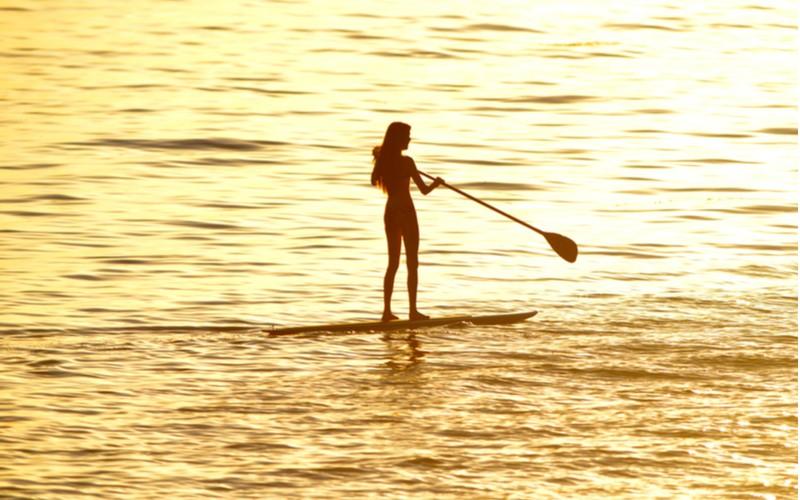 Osoba stojící na paddleboard