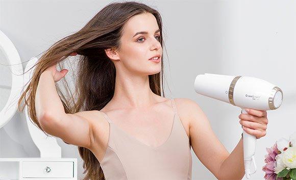 Žena si suší vlasy fénem Wellneo 2v1 AirPro