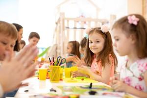 děti ve školce malují za stolem