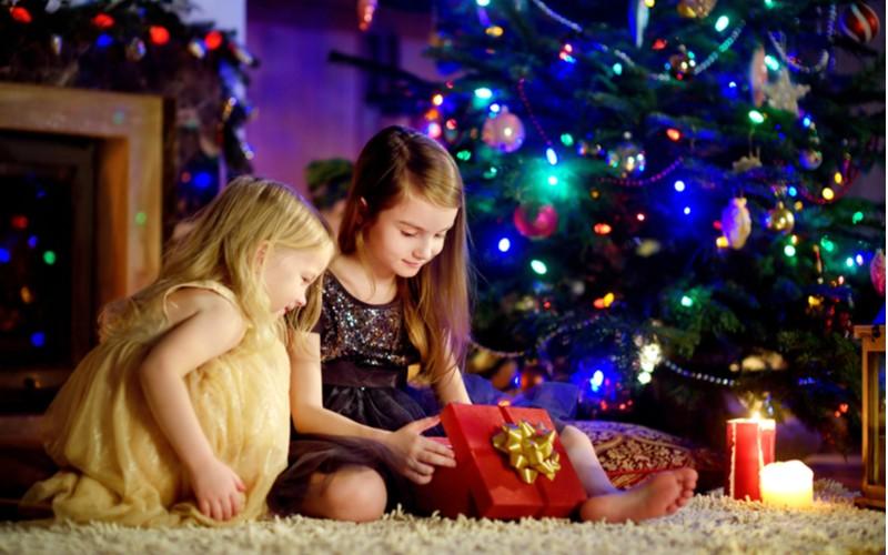 Dvě holčičky si rozbalují vánoční dárky