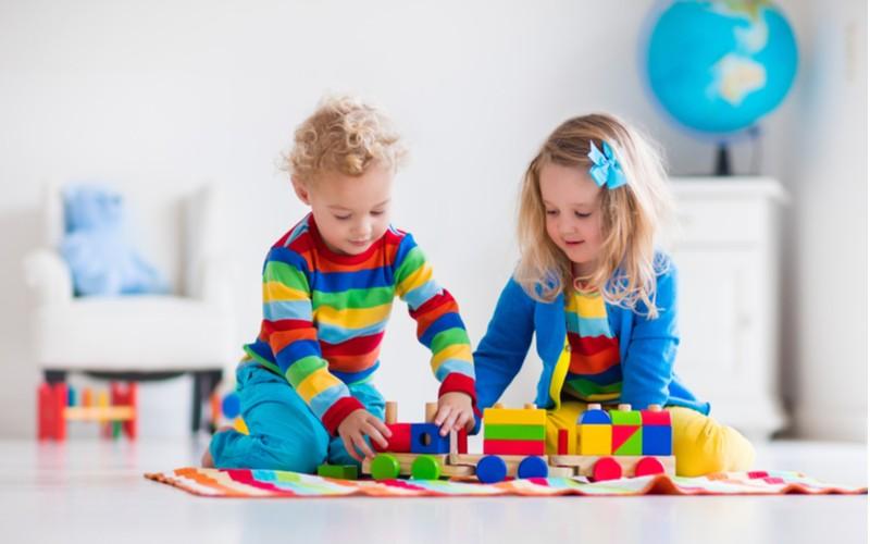 Holčička s chlapcem se hrají s dřevěným vláčkem