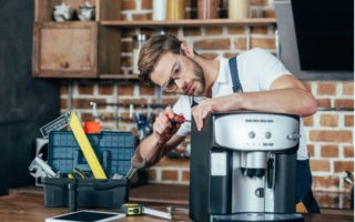 muž opravuje kávovar