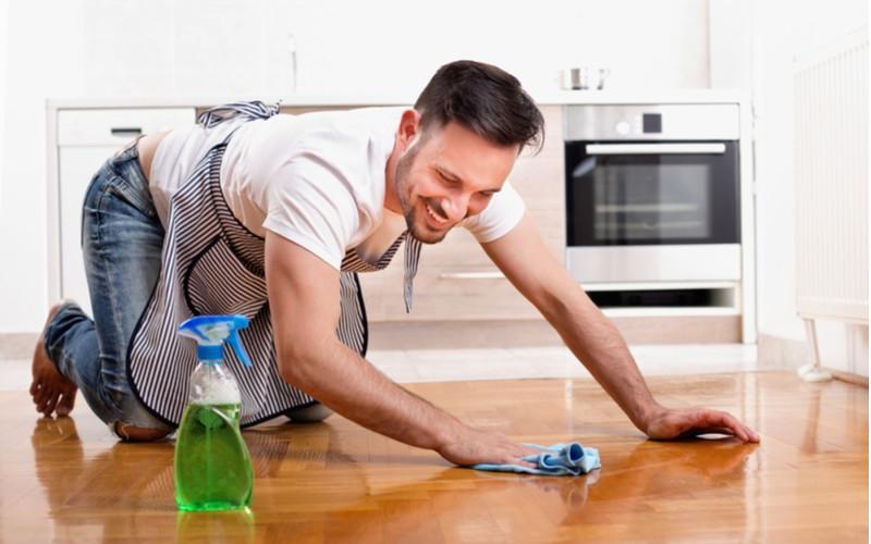 Usměvavý muž uklízí domácnost