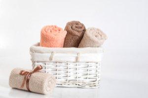Čtyři barevné ručníky, tři v košíku