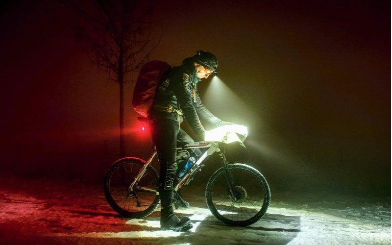 Cyklista si ve tmě svítí na mapu
