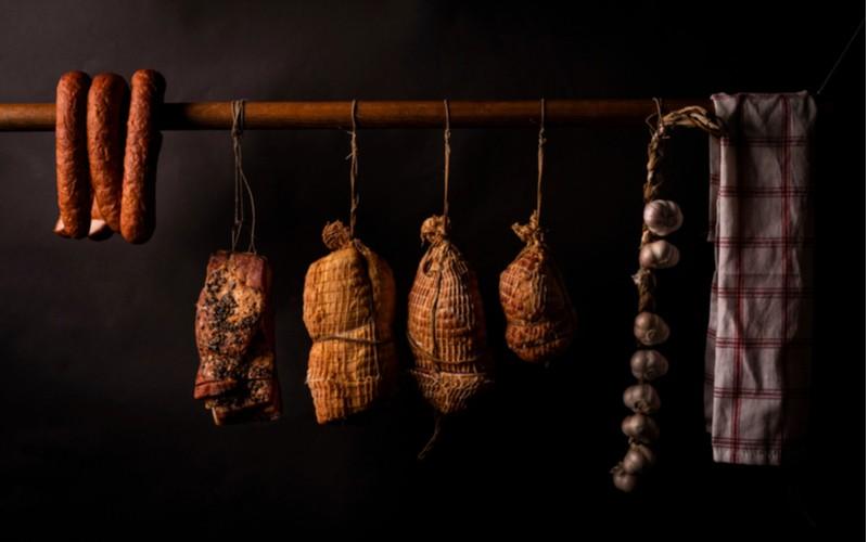 Šunka, slanina a klobása se udí na dřevě