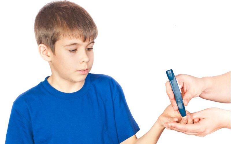 Chlapec v modrém tričku s glukometrem