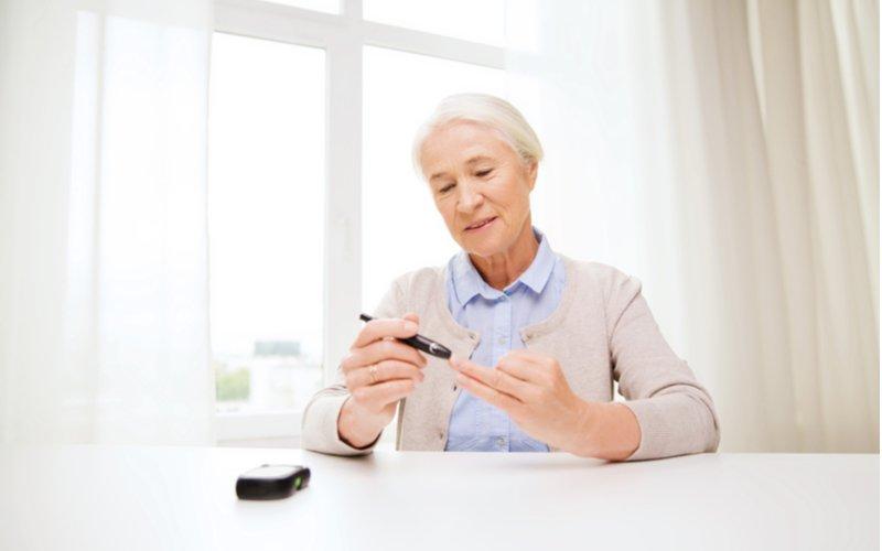 Starší paní si měří hladinu glukózy