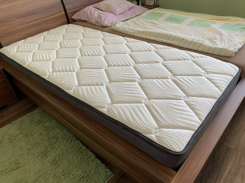 Jednolůžko bílá matrace na posteli