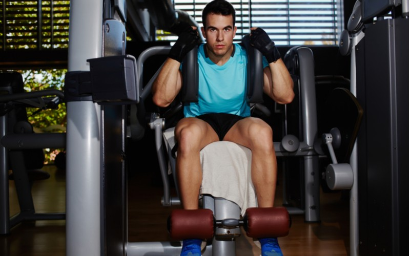 muž cvičí na posilovači břicha
